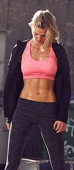 Woman looking at her six-pack abs earned at the best gyms in Albuquerque